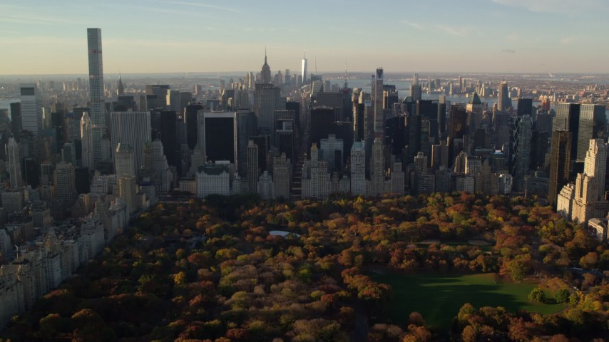 6K stock footage aerial video approaching Central Park with Autumn leaves and Midtown at sunrise in New York City Aerial Stock Footage | AX118_195