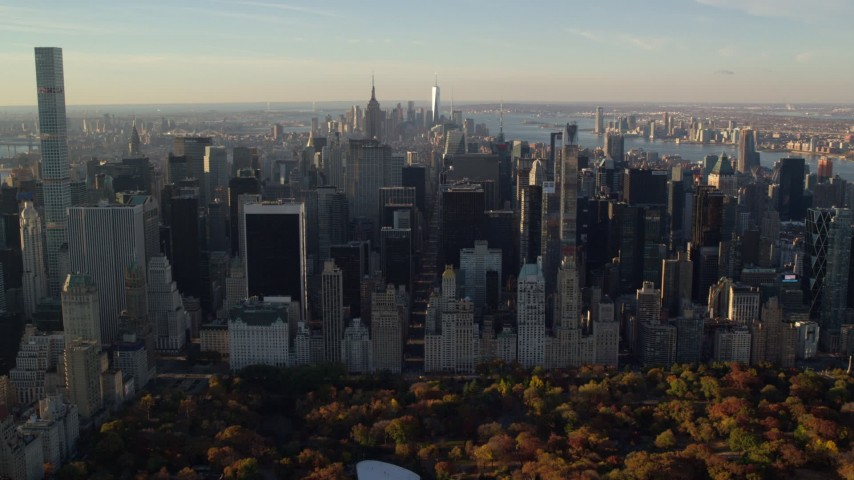 6K stock footage aerial video of an approach to Midtown from Central Park with Autumn leaves at sunrise in New York City Aerial Stock Footage | AX118_196