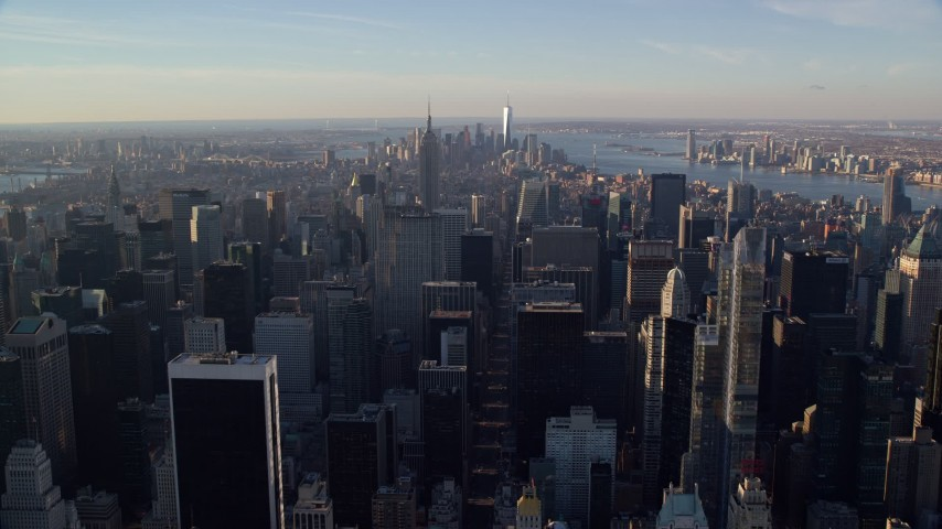 5.5K stock footage aerial video of Midtown skyscrapers at sunrise in New York City, with view of distant Lower Manhattan Aerial Stock Footage | AX118_197E