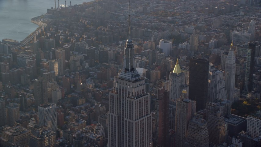 6K stock footage aerial video of orbiting the top of the Empire State Building at sunrise in New York City Aerial Stock Footage | AX118_204