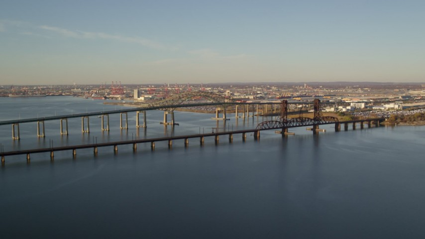 6K stock footage aerial video of flying by the Newark Bay Bridge and Lehigh Valley Bridge at sunrise in Newark, New Jersey Aerial Stock Footage | AX118_224