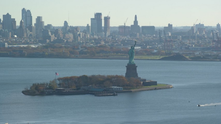 6K stock footage aerial video of the Statue of Liberty in Autumn, Brooklyn in the background, New York Aerial Stock Footage | AX119_009