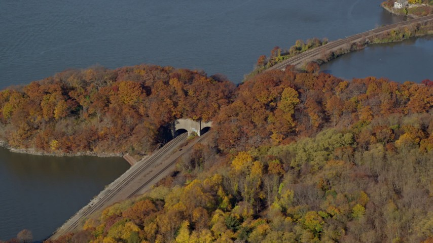 6K stock footage aerial video orbit riverfront railroad tracks and tunnel in Autumn, Croton on Hudson, New York Aerial Stock Footage | AX119_136
