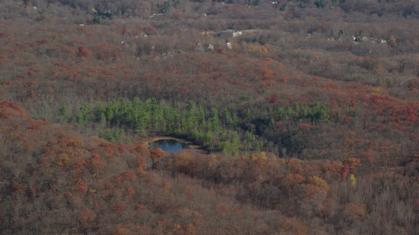 6K stock footage aerial video of a pond and forest in Autumn, Garrison, New York Aerial Stock Footage | AX119_192