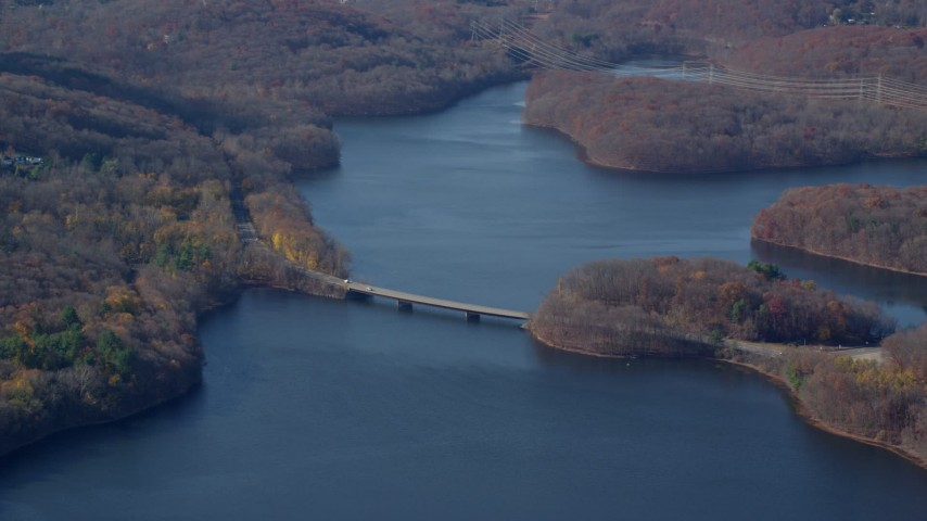 6K stock footage aerial video of small bridge over New Croton Reservoir in Autumn, New York Aerial Stock Footage AX119_207 | Axiom Images