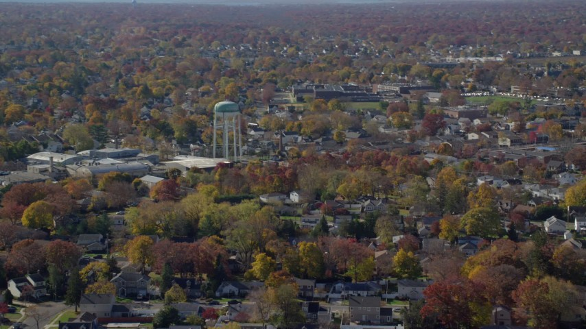 6K stock footage aerial video of a suburban residential neighborhood and water tower in Autumn, Farmingdale, New York Aerial Stock Footage | AX119_254