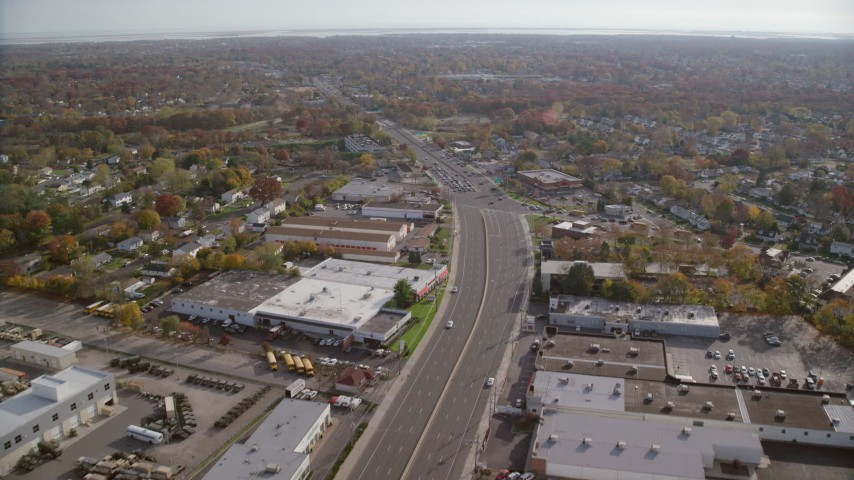 6K stock footage aerial video of warehouses on a wide street in Autumn, Farmingdale, New York Aerial Stock Footage | AX120_001