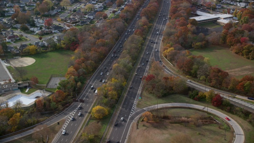 6K stock footage aerial video fly over freeway with light traffic in Autumn, Wantagh, New York Aerial Stock Footage | AX120_015