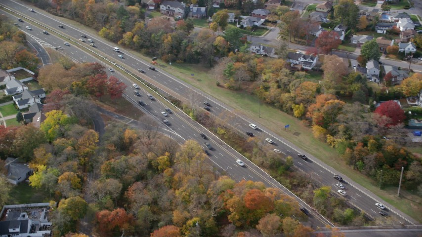 6K stock footage aerial video of light traffic cruising on a freeway in Autumn, Wantagh, New York Aerial Stock Footage | AX120_017
