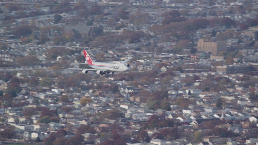 6K stock footage aerial video of a cargo plane descending toward JFK Airport, New York in Autumn Aerial Stock Footage | AX120_060