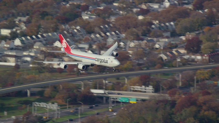 6K stock footage aerial video of a cargo plane descending toward JFK Airport, New York in Autumn Aerial Stock Footage | AX120_060E