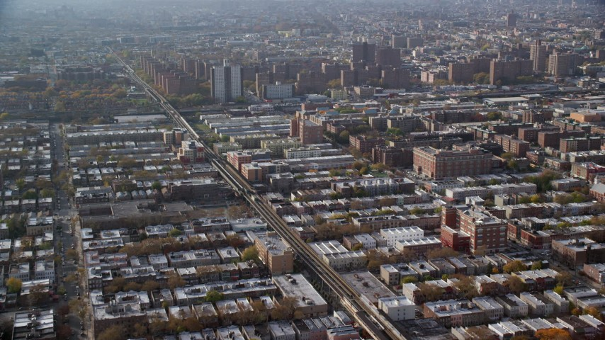 6K stock footage aerial video of row houses, elevated rail, and public housing in Autumn, Brooklyn, New York City Aerial Stock Footage | AX120_077