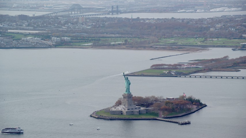 6K stock footage aerial video orbit the Statue of Liberty in Autumn, with New Jersey in the background, New York Aerial Stock Footage | AX120_120