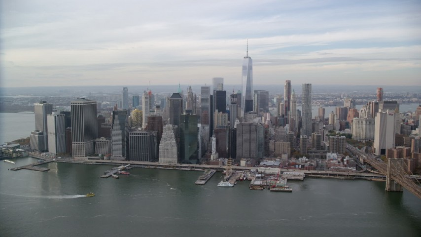 6K stock footage aerial video of crossing East River to approach skyscrapers in Autumn, Lower Manhattan, New York City Aerial Stock Footage | AX120_135