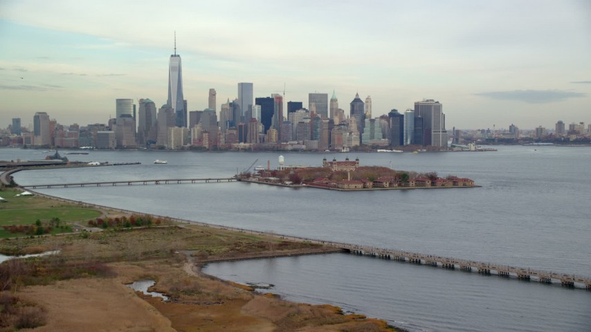 6K stock footage aerial video of Lower Manhattan and Ellis Island seen from Liberty Park in Autumn, New York City Aerial Stock Footage | AX120_261