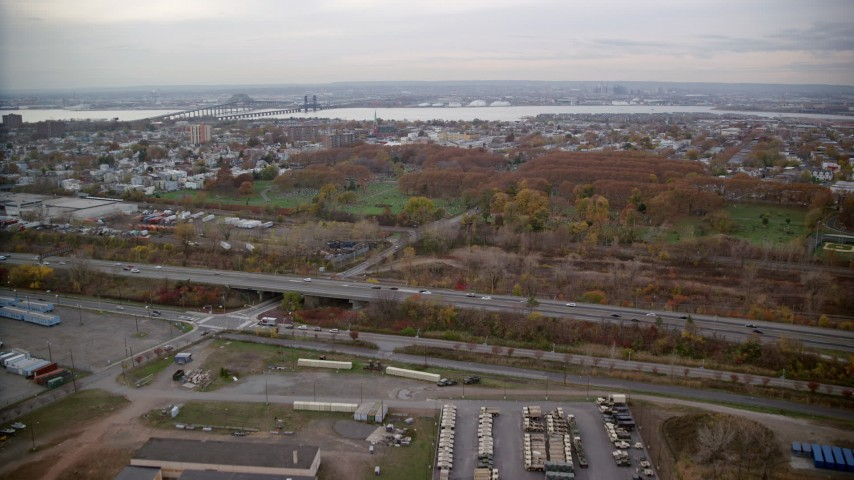 6K stock footage aerial video approach a Jersey City cemetery by a freeway in Autumn, New Jersey Aerial Stock Footage | AX120_265
