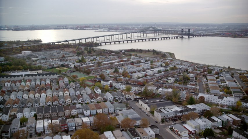 6K stock footage aerial video of suburban homes and row houses near bridges in Autumn, Jersey City, New Jersey Aerial Stock Footage | AX120_269