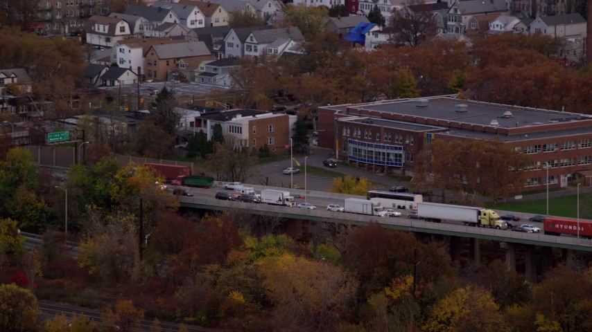 6K aerial video track ambulance on busy freeway at Sunset in Autumn, Bayonne, New Jersey Aerial Stock Footage AX121_007