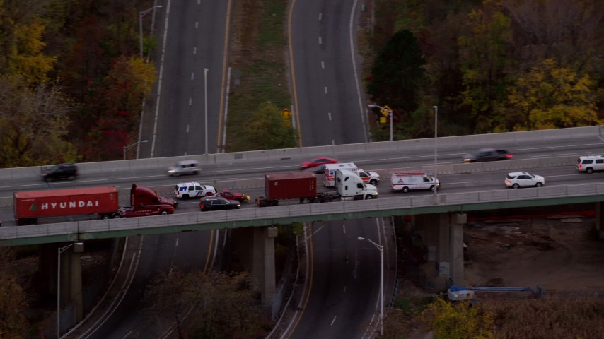 6K aerial video of an ambulance passing heavy freeway traffic at twilight, Bayonne, New Jersey Aerial Stock Footage | AX121_009