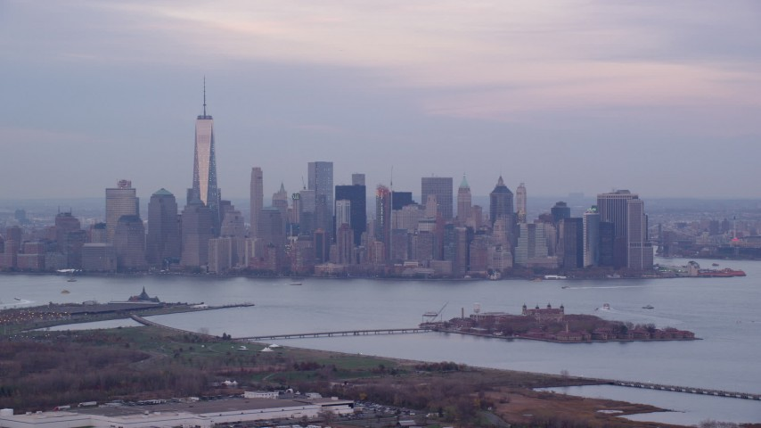 6K stock footage aerial video of Lower Manhattan skyline and Ellis Island at twilight in Autumn, New York City Aerial Stock Footage | AX121_011