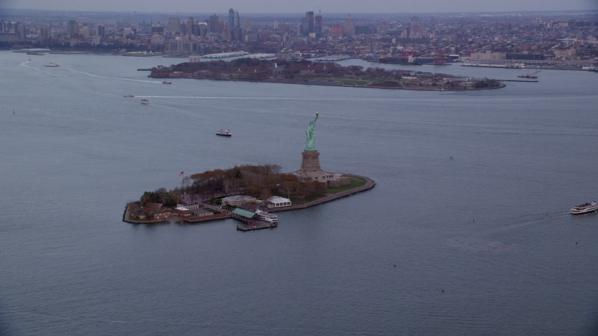 Orbit of Statue of Liberty at twilight in Autumn, New York Aerial Stock Footage | AX121_012