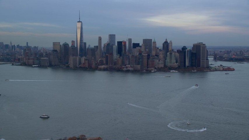 6K stock footage aerial video fly over Ellis Island toward Lower Manhattan skyline at twilight, New York City Aerial Stock Footage AX121_014 | Axiom Images