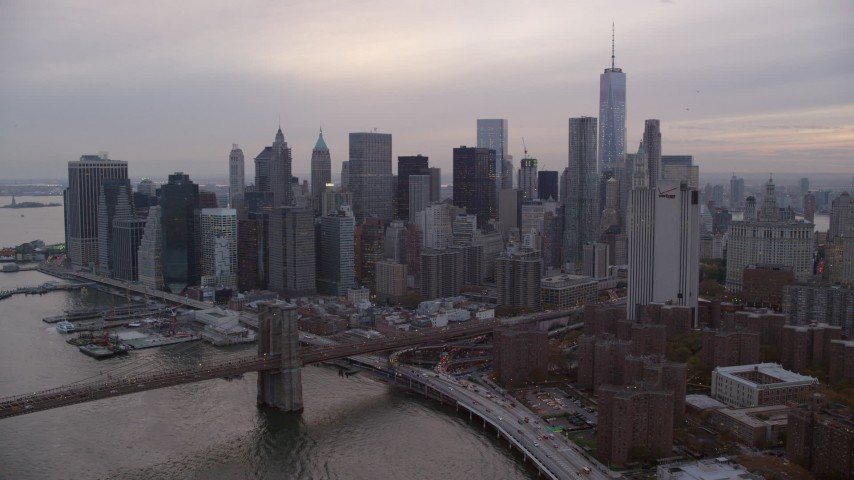 6K stock footage aerial video approach Lower Manhattan and the Brooklyn Bridge at twilight in New York City Aerial Stock Footage | AX121_030