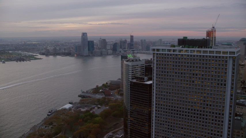 6K stock footage aerial video fly around skyscraper to reveal Downtown Jersey City from Lower Manhattan at twilight Aerial Stock Footage | AX121_034