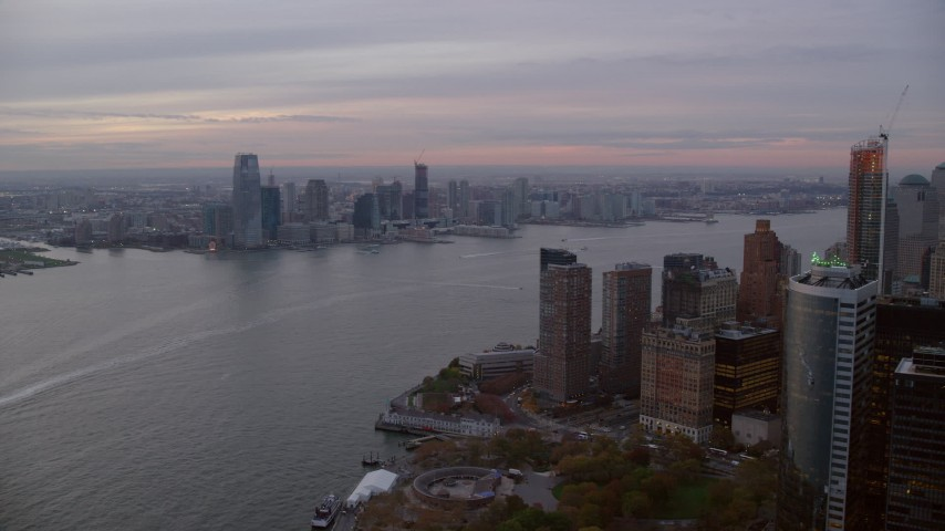 6K stock footage aerial video of Downtown Jersey City, New Jersey skyline at twilight, seen from Battery Park Aerial Stock Footage | AX121_035