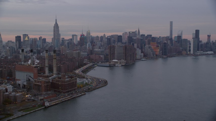 6K stock footage aerial video of an East Village power plant and Midtown skyscrapers at twilight in New York City Aerial Stock Footage | AX121_046