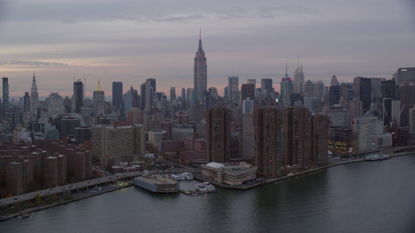 6K stock footage aerial video of riverfront Midtown high-rises and Empire State Building at twilight in New York City Aerial Stock Footage | AX121_048