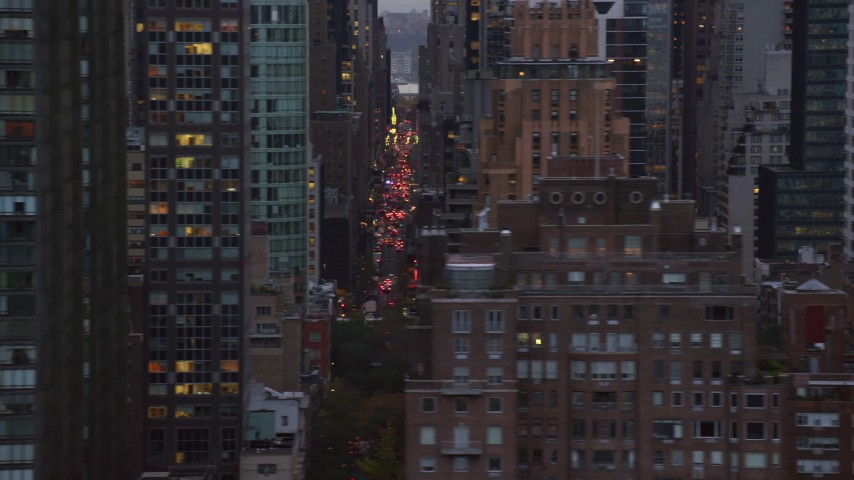 6K aerial video of passing skyscrapers and city streets in Midtown at twilight in New York City Aerial Stock Footage | AX121_054