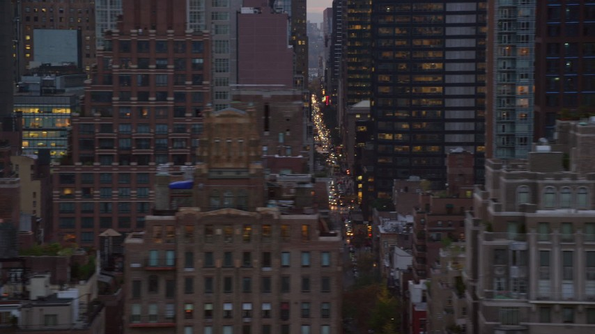 6K stock footage aerial video of passing high-rises and streets in Midtown at twilight in New York City Aerial Stock Footage | AX121_055