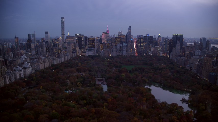 6K stock footage aerial video of Midtown skyscrapers seen from The Lake in Central Park at twilight, New York City Aerial Stock Footage | AX121_098