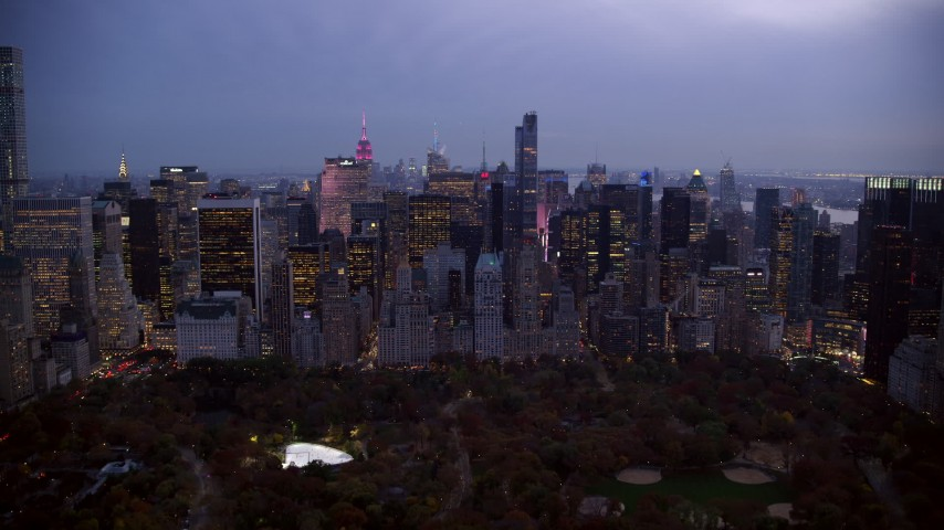 6K stock footage aerial video fly over Central Park to skyscrapers in Midtown at twilight in New York City Aerial Stock Footage | AX121_100