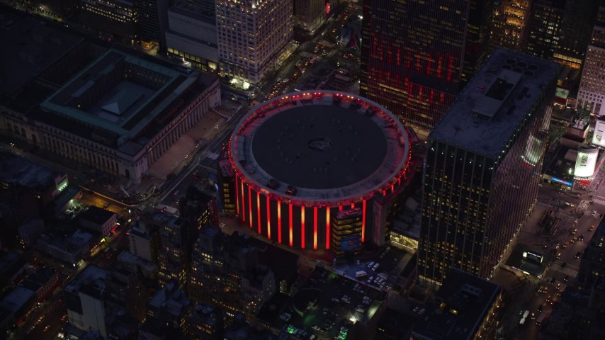 Orbit of Madison Square Garden at twilight in Midtown Manhattan Aerial Stock Footage | AX121_129