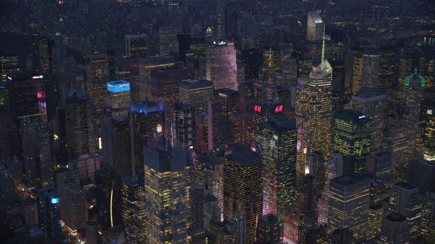 6K stock footage aerial video orbit Midtown skyscrapers to reveal part of Times Square at night, New York City Aerial Stock Footage | AX121_131