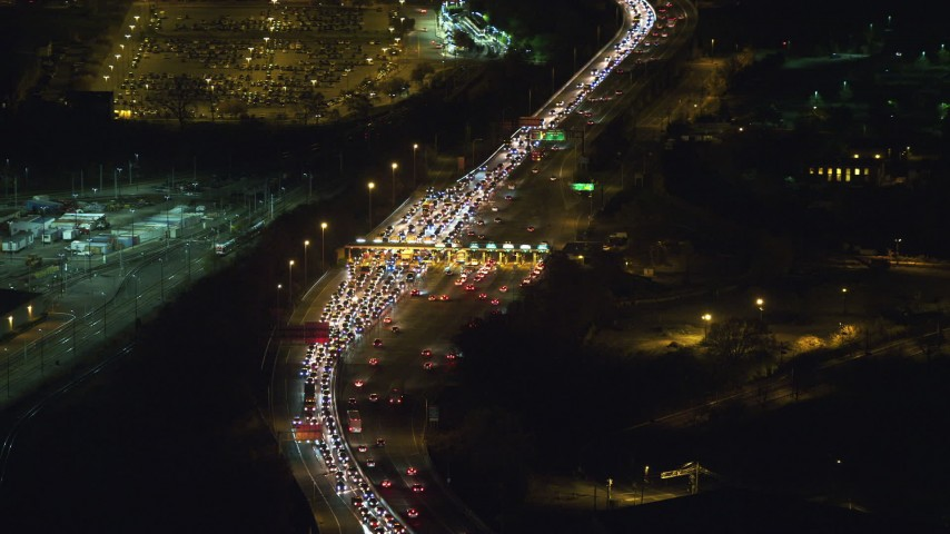 6K aerial video of orbiting heavy traffic at a Jersey City toll station at Night Aerial Stock Footage | AX121_199