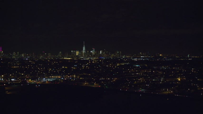 Lower Manhattan Seen from Jersey City Neighborhoods at Night Aerial Stock Footage | AX122_002