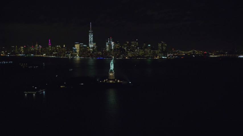 6K stock footage aerial video of the Statue of Liberty and the Lower Manhattan skyline at Night in New York Aerial Stock Footage | AX122_011