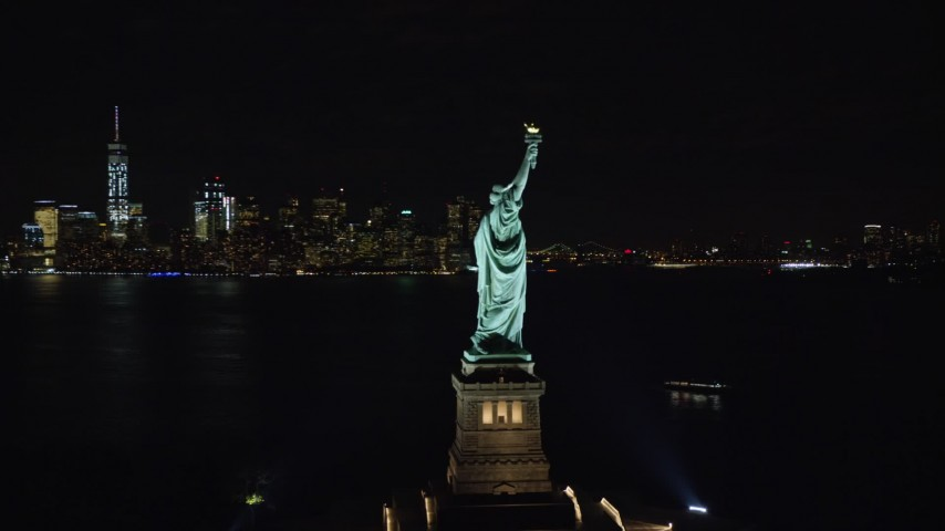 5.5K stock footage aerial video of an orbit around the side of the Statue of Liberty at Night in New York Aerial Stock Footage | AX122_020E