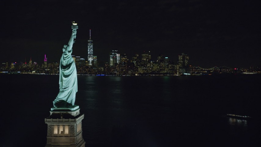 6K stock footage aerial video of Statue of Liberty and Lower Manhattan skyline at Night, New York Aerial Stock Footage | AX122_022
