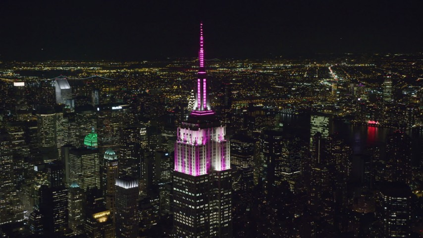 6K stock footage aerial video orbit the roof of Empire State Building as lighting comes on at Night in Midtown, NYC Aerial Stock Footage | AX122_086