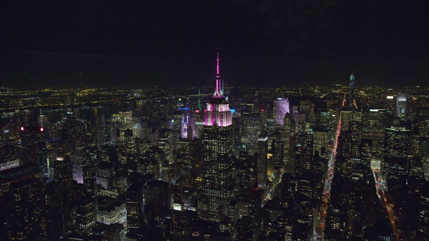 6K stock footage aerial video orbit Empire State Building with striped lighting at Night in Midtown Manhattan, NYC Aerial Stock Footage | AX122_091