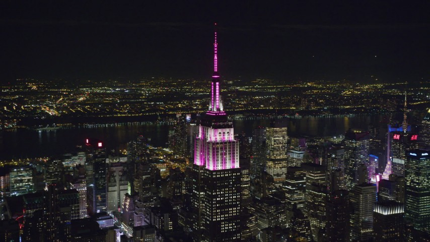 6K stock footage aerial video orbit top of Empire State Building with pink and white light at Night, Midtown Manhattan, NYC Aerial Stock Footage | AX122_093