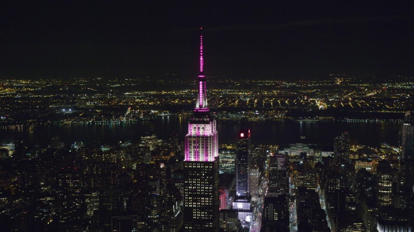 6K stock footage aerial video orbit the Empire State Building with pink and white lights at Night in Midtown, New York City Aerial Stock Footage   AX122_094