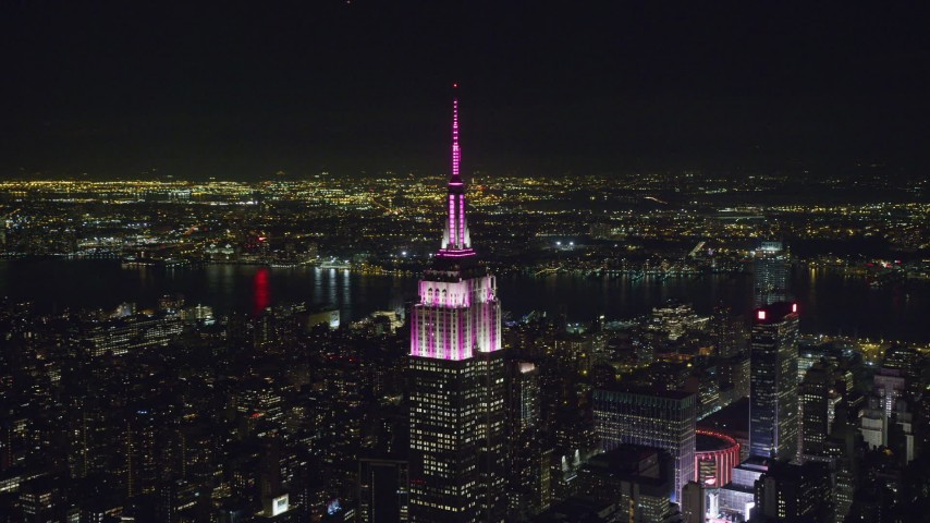 6K stock footage aerial video orbit Empire State Building with striped lighting at Night in Midtown Manhattan, NYC Aerial Stock Footage | AX122_095