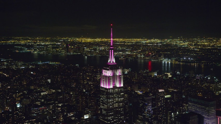 6K stock footage aerial video of orbiting Empire State Building with striped lights at Night, Midtown Manhattan, New York City Aerial Stock Footage | AX122_096