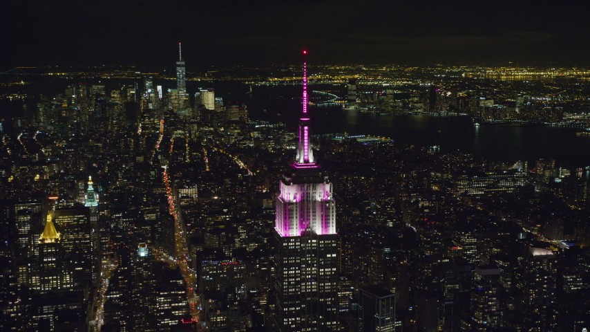 6K stock footage aerial video orbit of the Empire State Building with striped lights at Night, Midtown, NYC Aerial Stock Footage | AX122_097