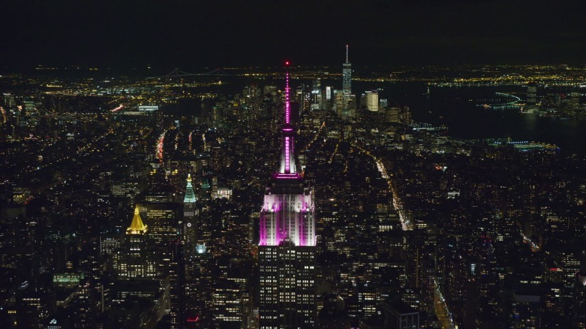 6K stock footage aerial video orbit of Empire State Building with striped lighting at Night in Midtown, NYC Aerial Stock Footage | AX122_098